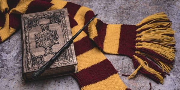 Scarf, magic wand, book of spells on grey stone background