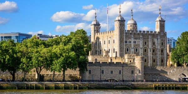 View of the Tower of London, a castle and a former prison in London, England, from the River Thames