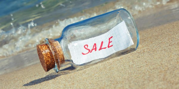 Message in a bottle on a beach with the word sale inside