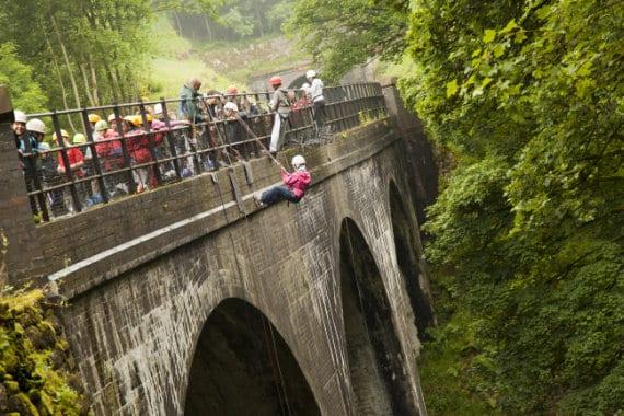 Children abseiling over a bridge