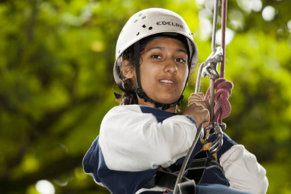 Teenage girl abseiling on a school trip at YHA