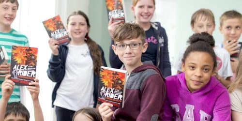 Children holding up Alex Rider books