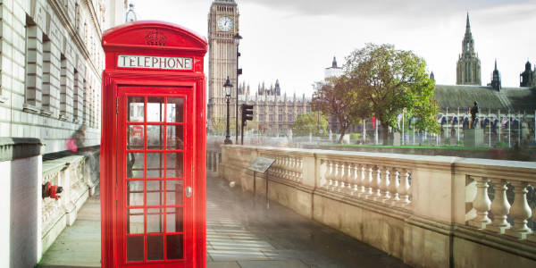 A red telephone box in front of Big Ben in London, UK