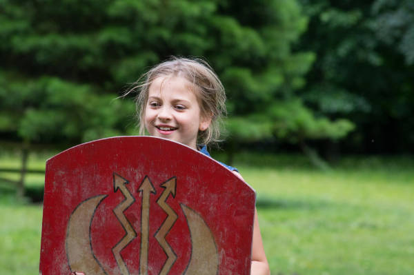 Young school girl holding a shield on a school trip