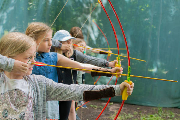 Girls at archery range with bow and arrows